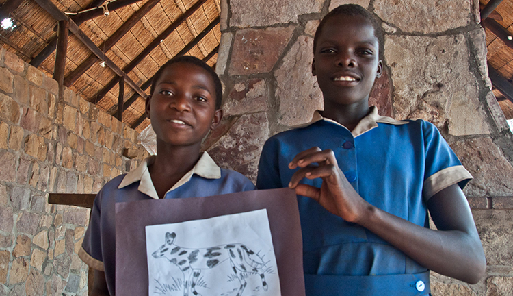Two children holding up a drawing of a Wild Dog