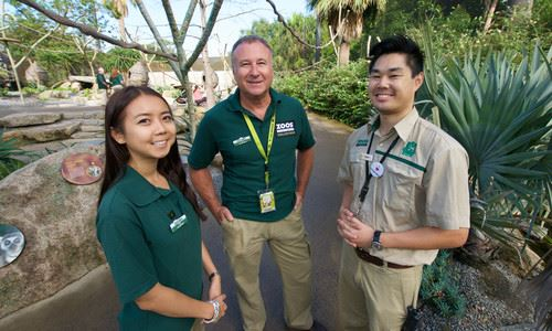 Two volunteers and a zoo keeper standing together at Melbourne Zoo