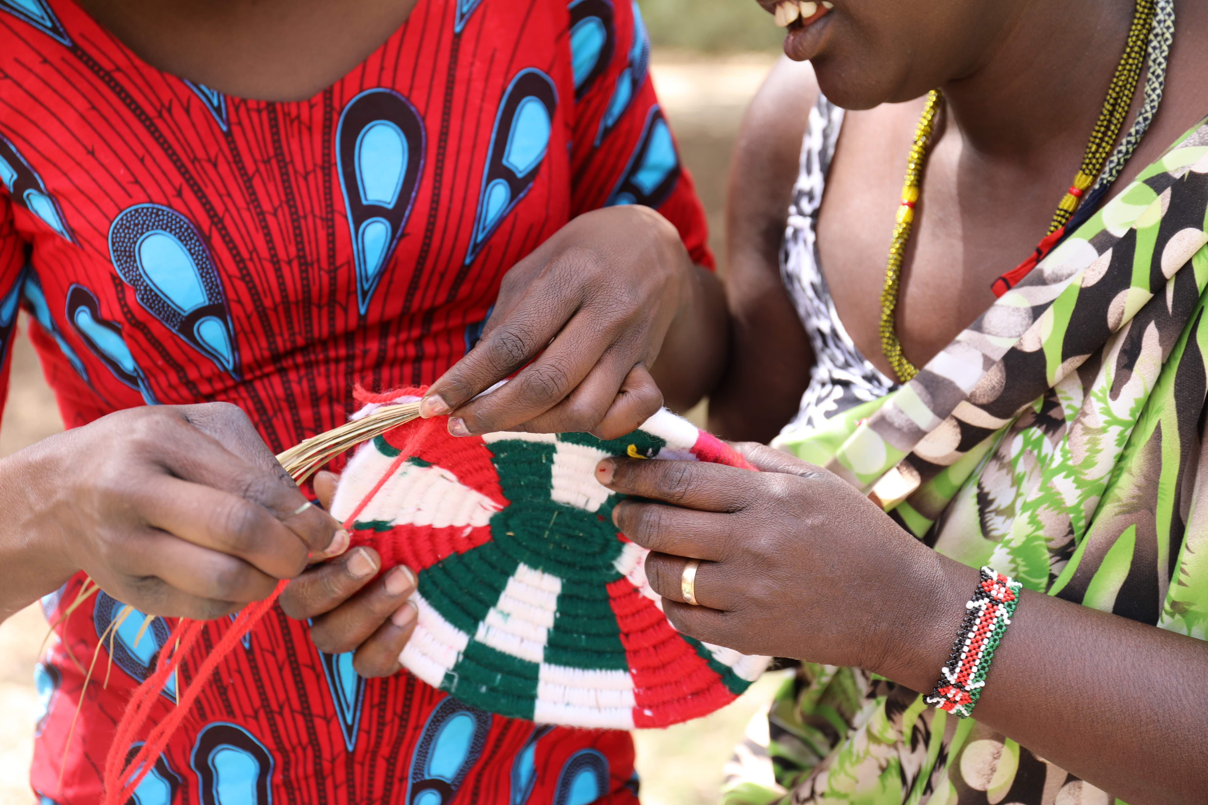Two women in colourful dresses working together to weave handmade basket